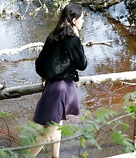 Teenage brunette peeing into a river in the park